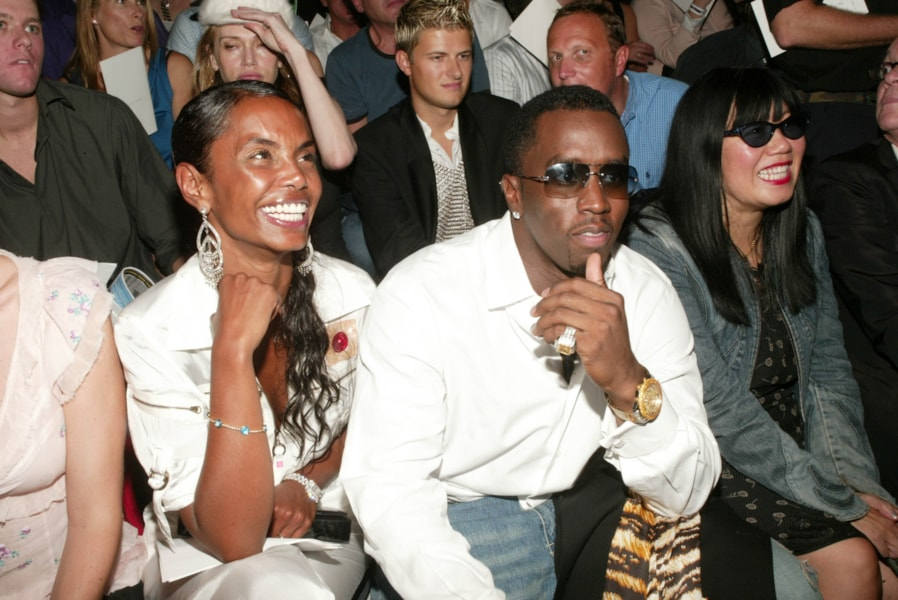 """NEW YORK - SEPTEMBER 15: (HOLLYWOOD REPORTER OUT) Sean """"P. Diddy"""" Combs and girlfriend Kim Porter attend the Marc Jacobs Spring/Summer 2004 Collection at the Manhattan Armory during the 7th on Sixth Mercedes-Benz Fashion Week on September 15, 2003 in New York City. (Photo by Evan Agostini/Getty Images)"""