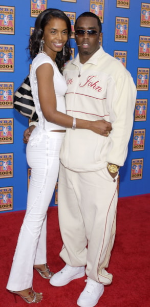 """LOS ANGELES - FEBRUARY 15:  Recording artist and producer Sean """"P Diddy"""" Combs with his girlfriend Kim Porter attend the 2004 NBA All-Star Game held on February 15, 2004 at the Staples Center, in Los Angeles, California. (Photo by Vince Bucci/Getty Images)"""