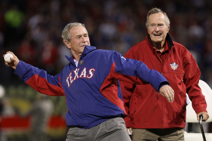 ARLINGTON, TX - OCTOBER 31:  Former President of the United States, George W. Bush, throws out the first pitch as his father Former President George H.W. Bush looks on before the Texas Rangers host the San Francisco Giants in Game Four of the 2010 MLB World Series at Rangers Ballpark in Arlington on October 31, 2010 in Arlington, Texas.  (Photo by Elsa/Getty Images)