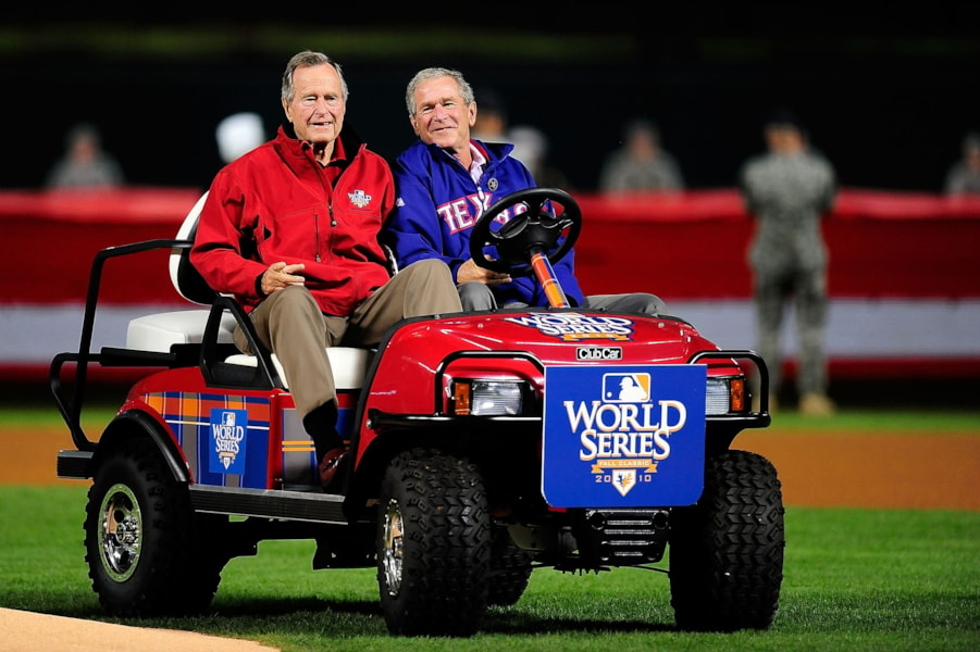 ARLINGTON, TX - OCTOBER 31:  Former President of the United States, George W. Bush (R), and his father Former President George H.W. Bush drive onto the field prior to the Texas Rangers host the San Francisco Giants in Game Four of the 2010 MLB World Series at Rangers Ballpark in Arlington on October 31, 2010 in Arlington, Texas.  (Photo by Pool/Getty Images)