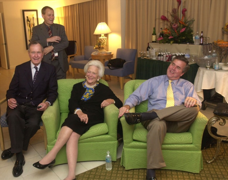 MIAMI - NOVEMBER 5:  Republican Florida Governor Jeb Bush (R) and his parents, former President George and Barbara Bush, await election returns November 5, 2002 in their Miami, Florida hotel room.  Bush is facing Democratic challenger Bill McBride, a Tampa lawyer. Victory for Bush would make him the first Republican governor re-elected in state history. In the background is Bush campaign communications director Todd Harris. (Photo by Joe Burbank/Pool/Getty Images)
