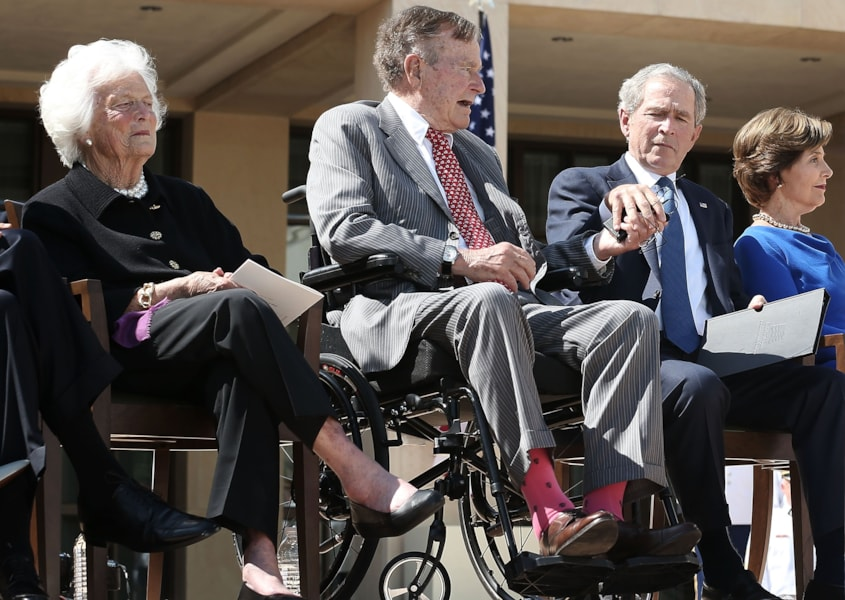 DALLAS, TX - APRIL 25:  Former U.S. President George W. Bush (2nd R) helps his father former President George H.W. Bush (2nd L) to take off his wireless microphone as they attend the opening ceremony of the George W. Bush Presidential Center with his wife, former first lady Laura Bush (R), and his mother, former first lady Barbara Bush, April 25, 2013 in Dallas, Texas. The Bush library, which is located on the campus of Southern Methodist University, with more than 70 million pages of paper records, 43,000 artifacts, 200 million emails and four million digital photographs, will be opened to the public on May 1, 2013. The library is the 13th presidential library in the National Archives and Records Administration system.  (Photo by Alex Wong/Getty Images)