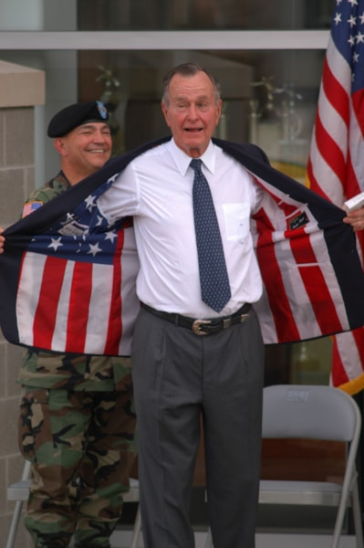 FORT BRAGG, NC - MAY 13:  George H.W. Bush, 41st President of the United States, flashes the inside of his jacket, containing an American flag, at the Brigadier General Joseph Stilwell Headquarters dedication ceremony May 13, 2004 in Fort Bragg, North Carolina. The headquarters contains history awards and exhibits on the Golden Knights, the U.S. Army Parachute Team.  (Photo by Logan Mock-Bunting/Getty Images)