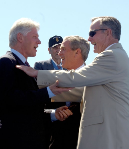 WASHINGTON - MAY 29:  Former U.S. President Bill Clinton (L) shares a laugh with former U.S. President George H.W. Bush (R) alongside U.S. President George W. Bush (C) on stage at the dedication of the World War II Memorial on May 29, 2004 in Washington, DC. The memorial was finished 59 years after the Allies victory in Europe and Japan in honor of the 16 million who served in World War II and those who died.  (Photo by Ron Sachs-Pool/Getty Images)