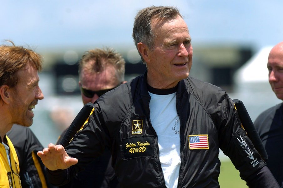 COLLEGE STATION, TX - JUNE 13:  Former U.S. President George Bush smiles with actor Chuck Norris (L) after completing a parachute jump to celebrate his 80th birthday June 13, 2004 in College Station, Texas. Bush planned to skydive alone, but officials decided high winds and low clouds made conditions too dangerous for him to take a solo jump.  (Photo by Brett Coomer/Getty Images)
