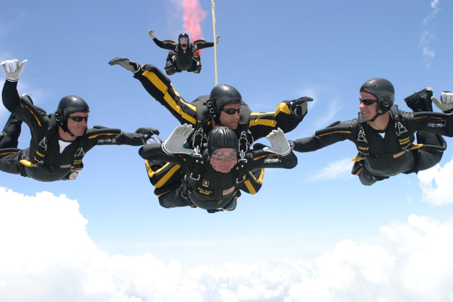 COLLEGE STATION, TX - JUNE 13:  Former U.S. President George H.W. Bush (C, bottom) performs a tandem parachute jump with Army Golden Knight Sgt. Bryan Schnell on June 13, 2004 over the Bush Presidential Library in College Station, Texas.  Bush made two jumps today to celebrate his 80th birthday.  (Photo by U.S. Army/Texas A&M University via Getty Images)