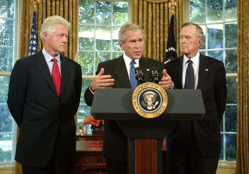 WASHINGTON - SEPTEMBER 1:  U.S. President George W. Bush (C) announces that he appointed former U.S. Presidents Bill Clinton (L) and George H. W. Bush to lead a fund-raising effort for victims of Hurricane Katrina at the White House September 1, 2005 in Washington, DC. Rescue efforts continue as officials in New Orleans fear the death toll from Hurricane Katrina could be in the thousands.  (Photo by Ron Sachs-Pool/Getty Images)