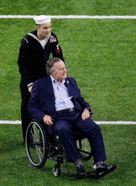HOUSTON, TX - FEBRUARY 05:  Former US President George H. W. Bush is helped to midfield for the coin toss prior to Super Bowl 51 between the New England Patriots and the Atlanta Falcons at NRG Stadium on February 5, 2017 in Houston, Texas.  (Photo by Bob Levey/Getty Images)