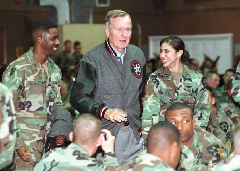 397102 02: Former U.S. President George Bush (C) speaks with U.S. soldiers during a United Services Organization (USO) event November 9 2001 at Camp Casey, which is located 31 miles north of Seoul South Korea. Bush attended the opening ceremony of the newly renovated USO building at the camp. (Photo by Chung Sung-Jun/Getty Images)