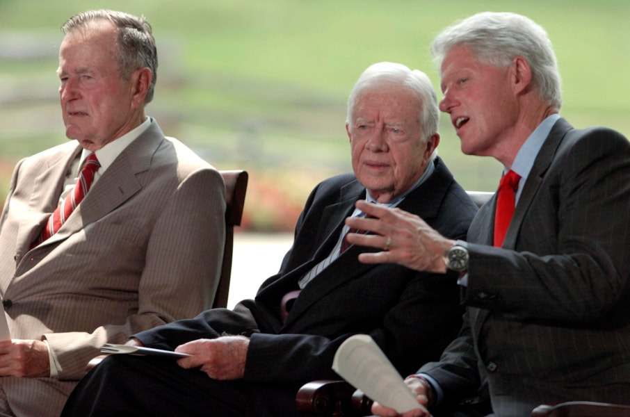 CHARLOTTE, NC - MAY 31:  Former U.S. Presidents Jimmy Carter (C) and Bill Clinton, (R) talk as George H.W. Bush listens to remarks on the stage during the Billy Graham Library Dedication Service on May 31, 2007 in Charlotte, North Carolina. Approximately 1500 guests attended the private dedication ceremony for the library, which chronicles the life and teachings of Evangelist Billy Graham. All three former Presidents spoke during the ceremony. (Photo by Davis Turner/Getty Images)