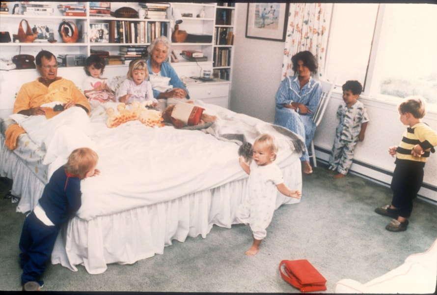 374836 01: George Bush and his wife Barbara sit in their bed as six of their fourteen grandchildren play around them in Washington, D.C. Bush was born June 12, 1924 in Milton, Massachusetts. He attended both Phillips Academy in Andover and Yale University. (Photo by Liaison)