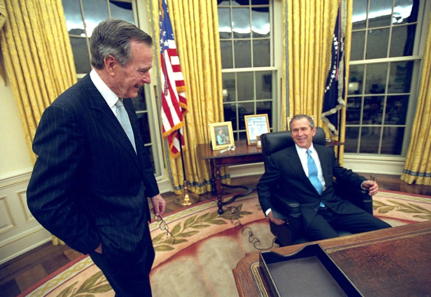 388434 10: (FILE PHOTO) President George W. Bush sits at his desk January 20, 2001 in the Oval Office for the first time on Inaugural Day. His father, former President George H.W. Bush, shares the moment. President Bush will celebrate his first 100 days in office April 29, 2001. (Photo by Eric Draper/White House/Newsmakers)