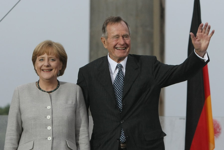 BERLIN - JULY 04:  Former U.S. President George Bush and German Chancellor Angela Merkel wave to visitors after speaking at the official opening of the new U.S. embassy on July 4, 2008 in Berlin, Germany. Architectural critics claim the embassy, designed by American architect Moore Ruble Yudell, offers little in architectural innovation or design.  (Photo by Sean Gallup/Getty Images)