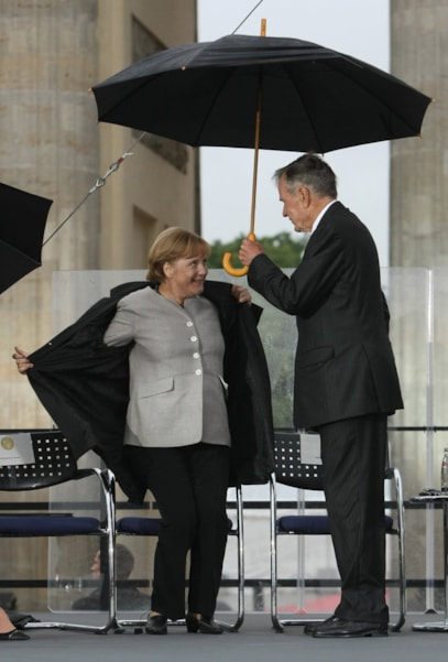 BERLIN - JULY 04:  German Chancellor Angela Merkel takes off her coat as former U.S. President George Bush holds an umbrella against the rain at the official opening of the new U.S. embassy on July 4, 2008 in Berlin, Germany. Architectural critics claim the embassy, designed by American architect Moore Ruble Yudell, offers little in architectural innovation or design.  (Photo by Sean Gallup/Getty Images)