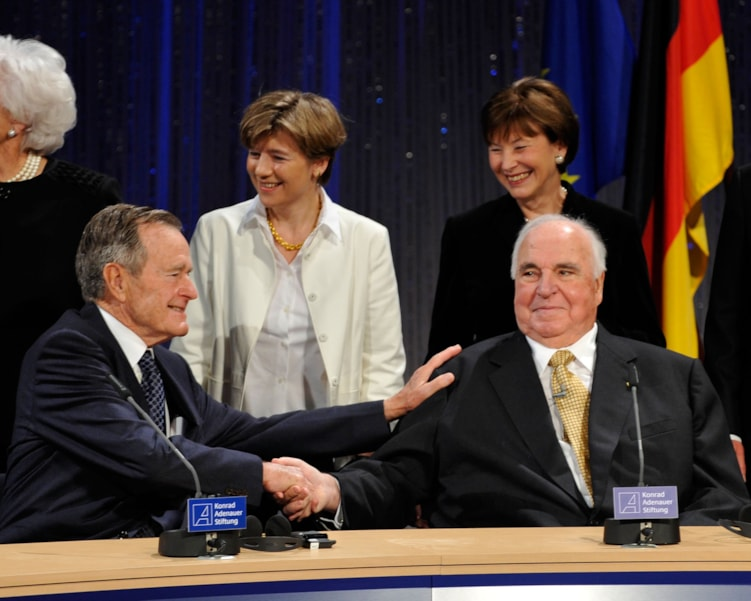 """BERLIN - OCTOBER 31:  Former US president George H. W. Bush (L) greats former German Chancellor Helmut Kohl as Kohls wife Maike Richter-Kohl and the wife of German President Horst Koehler, Eva Koehler, look on during an event at Friedrichstadtpalast on October 31, 2009 in Berlin, Germany. The event organized by The Konrad Adenauer Foundation takes place under the motto: """"The Fall of the Wall and Reunification - the Victory of Freedom."""" Bush, Gorbachev and Kohl played key roles as the peaceful revolution unfolded in East Germany in the autumn of 1989. Their cooperation would pave the way for German reunification in 1990.  (Photo by Steffen Kugler/Getty Images)"""
