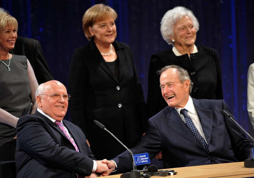 """BERLIN - OCTOBER 31:  Former US president George H. W. Bush (R) shakes hands with former soviet president Mikhail Gorbatchev as German Chancellor Angela Merkel and Bush's wife Barbara Bush (R) look on at an event at Friedrichstadtpalast on October 31, 2009 in Berlin, Germany. The event organized by The Konrad Adenauer Foundation takes place under the motto: """"The Fall of the Wall and Reunification - the Victory of Freedom."""" Bush, Gorbachev and Kohl played key roles as the peaceful revolution unfolded in East Germany in the autumn of 1989. Their cooperation would pave the way for German reunification in 1990.  (Photo by Steffen Kugler/Getty Images)"""